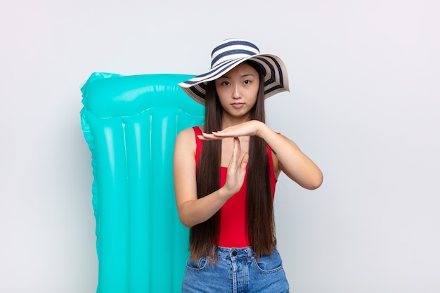 Asian young woman looking serious, stern, angry and displeased, making time out sign. summer concept