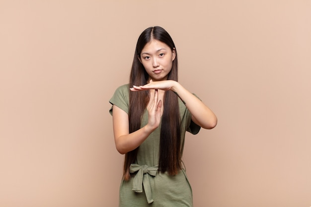 Asian young woman looking serious, stern, angry and displeased, making time out sign