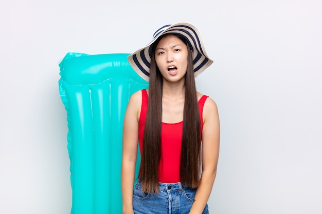 Asian young woman looking shocked, angry, annoyed