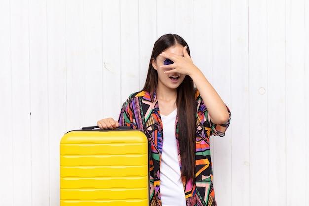 ショックを受けたり、怖がったり、おびえたりして、顔を手で覆い、指の間をのぞくアジアの若い女性。休日の概念
