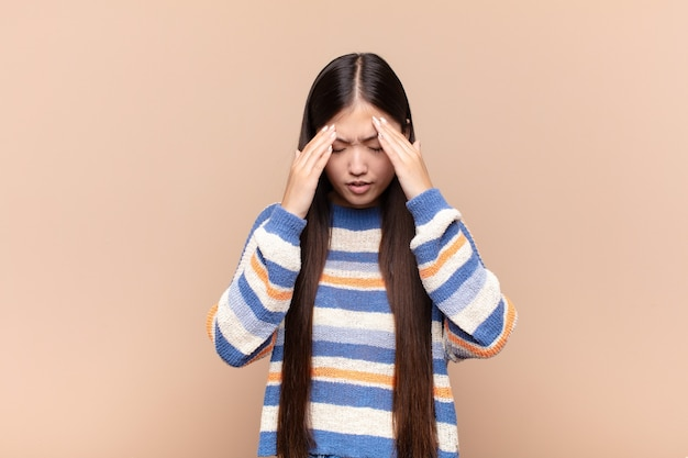 Азиатская молодая женщина, выглядящая подчеркнутой и разочарованной изолированной