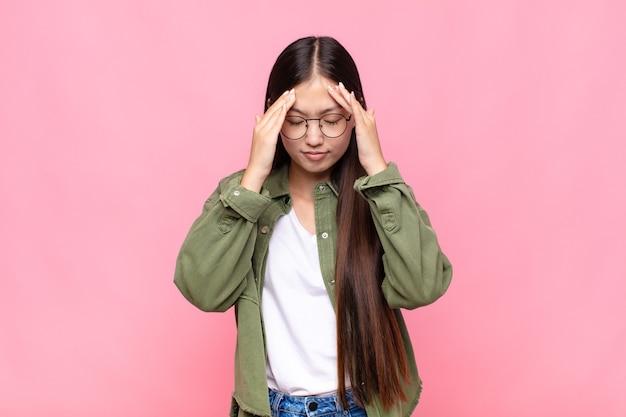 Азиатская молодая женщина выглядит напряженной и разочарованной, работает под давлением с головной болью и обеспокоена проблемами