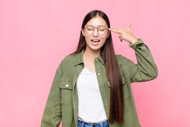 不幸でストレスを感じているアジアの若い女性、手で銃のサインを作る自殺ジェスチャー、頭を指して