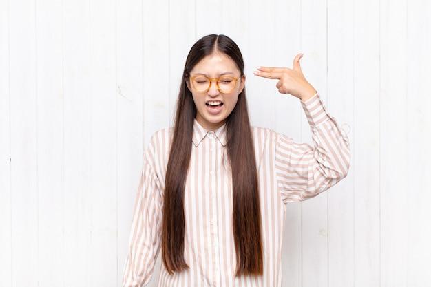 Азиатская молодая женщина выглядит несчастной и подчеркнутой, жест самоубийства делает знак пистолет рукой