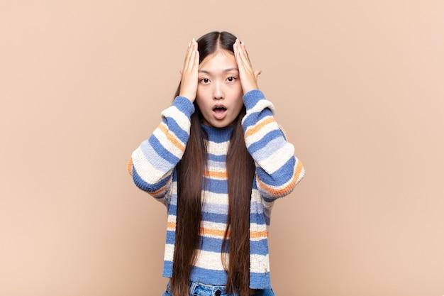 Азиатская молодая женщина выглядит неприятно шокированной, напуганной или обеспокоенной, с широко открытым ртом и закрывающей оба уха руками