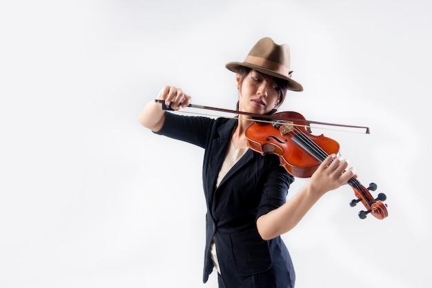 Азиатская молодая женщина-музыкант играет на скрипке классической музыки