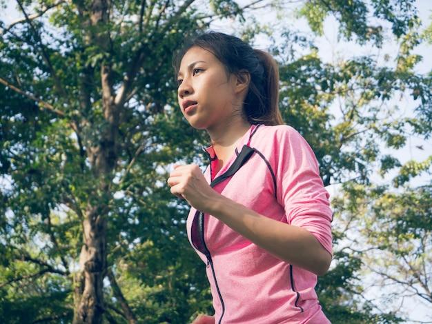 アジアの若い女性がジョギングの準備をするためのマーク運動