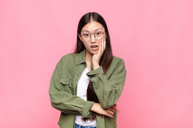 Asian young woman open-mouthed in shock and disbelief, with hand on cheek and arm crossed, feeling stupefied and amazed