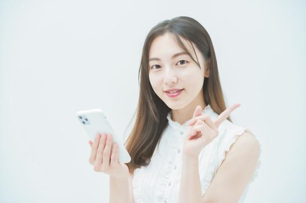 Азиатская молодая женщина, работающая со смартфоном