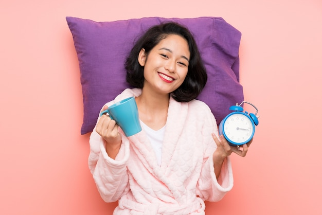 Asian young woman in pajamas holding a cup of coffee and a clock