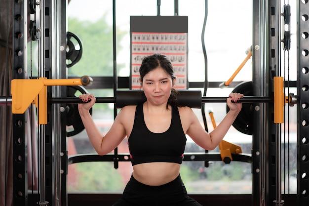 運動にジム機器を演奏するアジアの若い女性は、ジムで彼女のボデーだけを構築し、スポーティなボクシングジムコンセプトの健康的なライフスタイルアジアモデルに適合します。