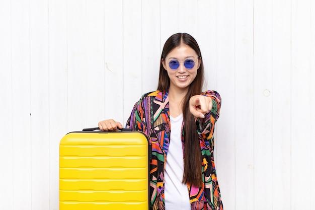 満足、自信を持って、フレンドリーな笑顔でカメラを指して、あなたを選ぶアジアの若い女性。休日の概念