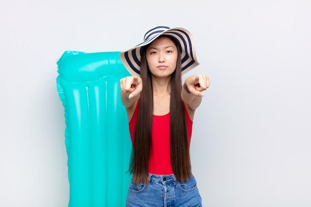 아시아 젊은 여자가 손가락과 화가 난 표정으로 카메라를 앞으로 가리키며 의무를 다하라고 말합니다. 여름 개념