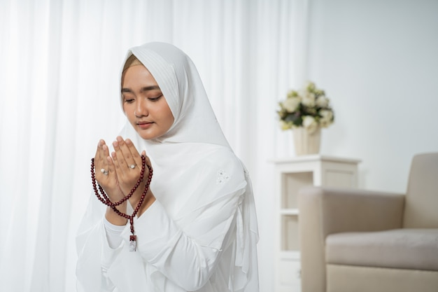 Asian young woman praying with al-qur'an and prayer beads