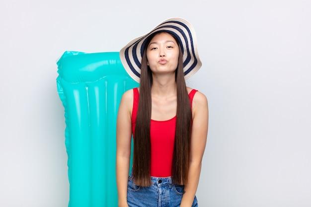 Азиатская молодая женщина, сжимая губы вместе, выглядит мило изолированные
