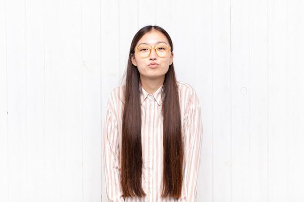 Азиатская молодая женщина сжимает губы вместе с милым, веселым, счастливым, прекрасным выражением лица, отправляя поцелуй