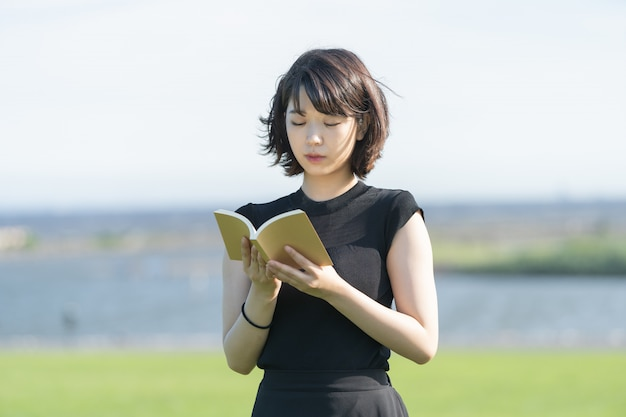 Asian young woman reading a book in the park