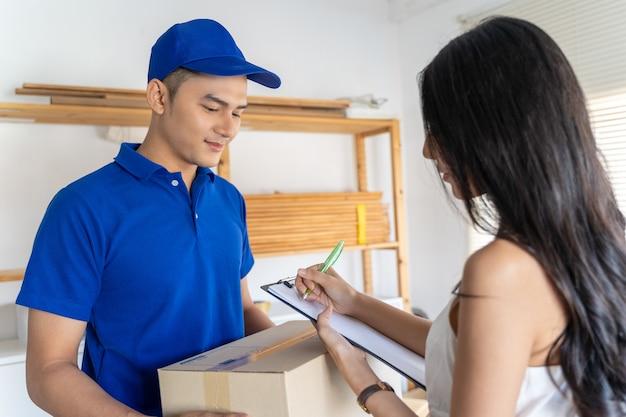 Азиатская молодая женщина получает пакет от доставщика. улыбающийся молодой курьер держит картонную коробку, пока красивая молодая женщина ставит подпись в буфере обмена