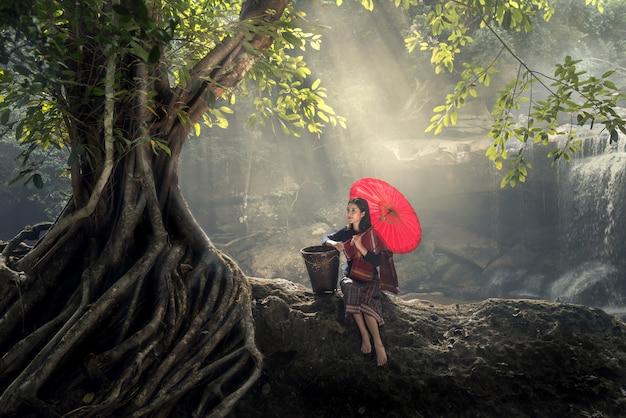 アジアの若い女性は自然でリラックスします。緑の森の中に赤い傘がある。