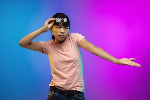 Ritratto di giovane donna asiatica su sfondo sfumato per studio in neon. bellissimo modello femminile in stile casual. Foto Gratuite