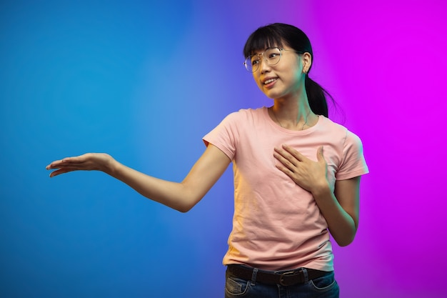 Asian young woman's portrait on gradient studio wall