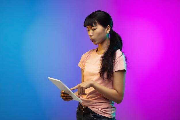 Портрет азиатской молодой женщины на фоне студии градиента в неоне. красивая женская модель в стиле casual.