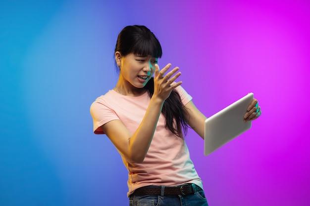 ネオンのグラデーションスタジオの背景にアジアの若い女性の肖像画。カジュアルなスタイルで美しい女性モデル。