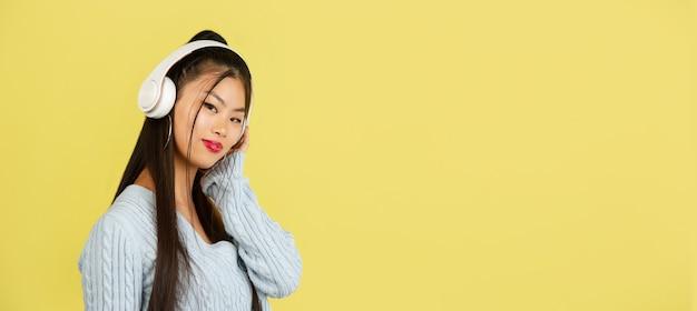Портрет азиатской молодой женщины на желтой студии с наушниками