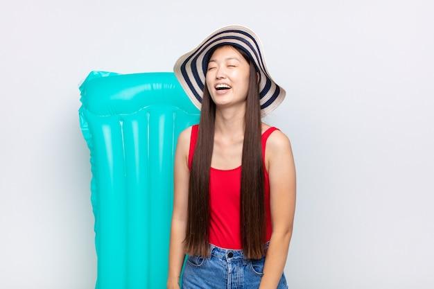 아시아 젊은 여성이 격렬하게 비명을 지르고, 공격적으로 외치고, 스트레스를 받고 화가납니다. 여름 개념