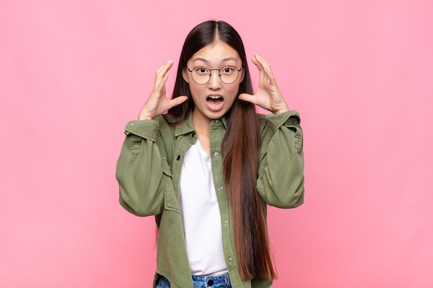 孤立した空中で手を上げて叫んでいるアジアの若い女性