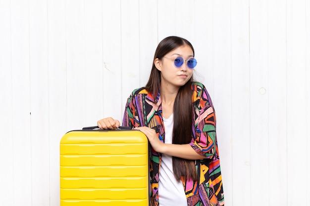 아시아 젊은 여성이 어깨를 으쓱하고, 혼란스럽고 불확실한 느낌, 팔로 의심하고 어리둥절한 표정. 휴일 개념