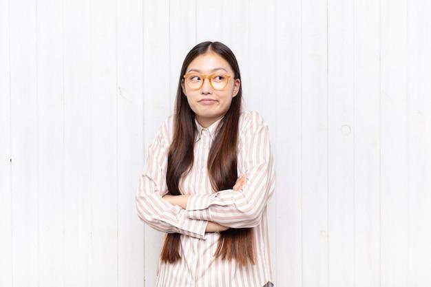 아시아 젊은 여성이 어깨를 으쓱하고, 혼란스럽고 불확실한 느낌, 팔로 의심하고 의아해 보이는 모습