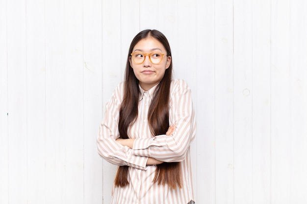 Asian young woman shrugging, feeling confused and uncertain, doubting with arms crossed and puzzled look