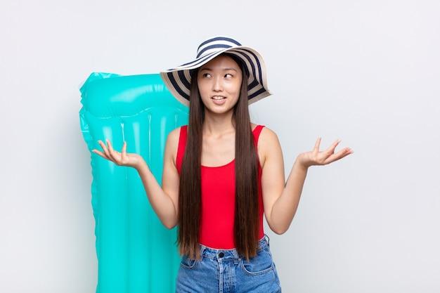 愚かで、狂った、混乱した、困惑した表情で肩をすくめるアジアの若い女性は、イライラして無知だと感じています。夏のコンセプト