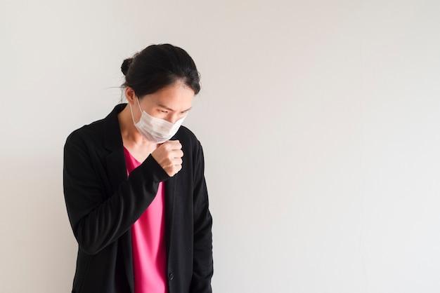Азиатская молодая женщина больна и носить маску