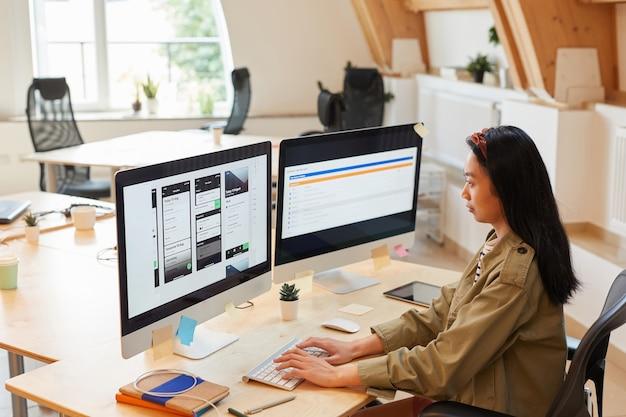 Азиатская молодая женщина сидит за столом и печатает на клавиатуре компьютера, она тестирует новое программное обеспечение в офисе