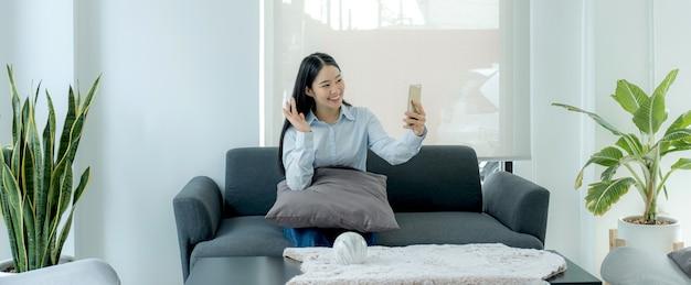 Азиатская молодая женщина сидит на диване дома по видеовызову делает жест рукой, чтобы поприветствовать разговор