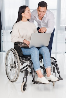 Asian young woman sitting on wheel chair looking at man showing something on laptop