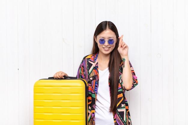 アジアの若い女性は笑顔で心配そうに両指を交差させ、心配を感じ、幸運を願ったり期待したりしています。休日の概念