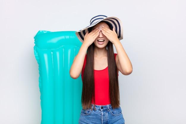 分離された両手で目を覆う、笑顔と幸せな気持ちのアジアの若い女性