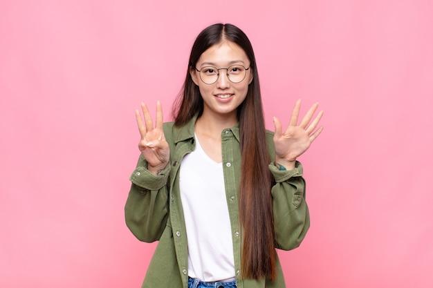 笑顔でフレンドリーに見えるアジアの若い女性、手前で8番または8番を示し、カウントダウン