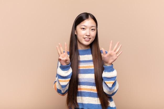 笑顔でフレンドリーに見えるアジアの若い女性、手前で8番または8番を示しています
