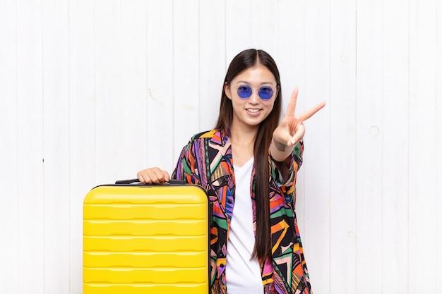 アジアの若い女性は笑顔で幸せそうに見え、のんきで前向きで、片手で勝利または平和を身振りで示します。休日の概念