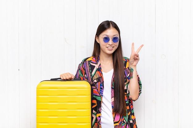 笑顔で幸せそうに見えるアジアの若い女性、友好的で満足し、両手で勝利または平和を身振りで示す。休日の概念