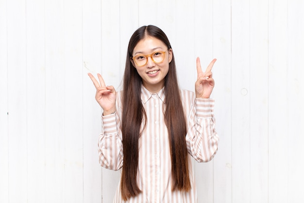 笑顔で幸せそうに見えるアジアの若い女性、友好的で満足し、両手で勝利または平和を身振りで示す