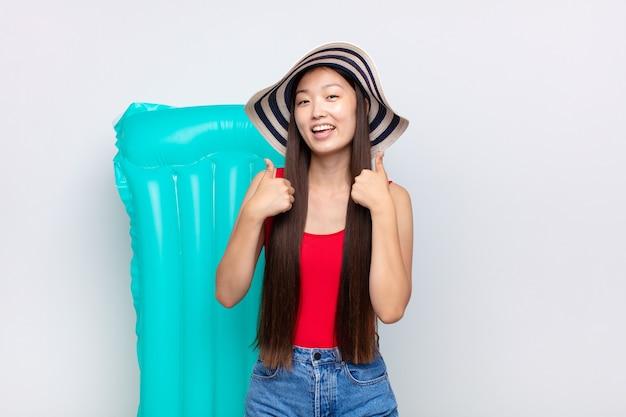 Азиатская молодая женщина, широко улыбаясь, выглядит счастливой, позитивной, уверенной и успешной, с двумя пальцами вверх. летняя концепция