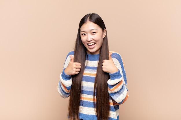 두 엄지 손가락으로 광범위하게 행복, 긍정적, 자신감과 성공을 찾고 웃는 아시아 젊은 여자