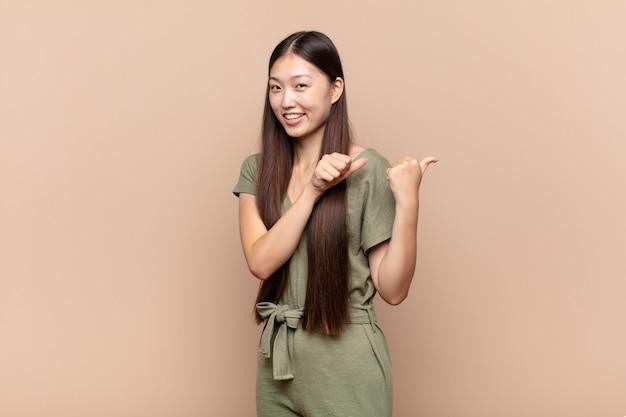 행복하고 만족스러운 느낌, 유쾌하고 부담없이 측면에 복사 공간을 가리키는 아시아 젊은 여자