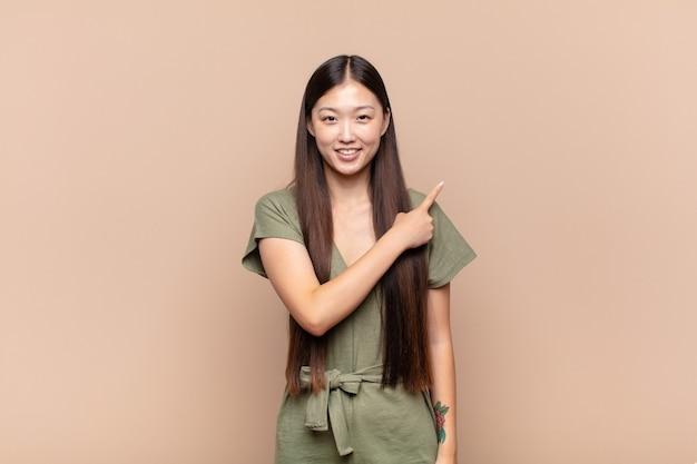 유쾌하게 웃고, 행복을 느끼고, 측면과 위쪽을 가리키는 아시아 젊은 여성, 복사 공간에 개체 표시