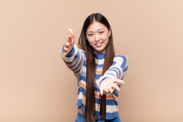 暖かく、フレンドリーで、愛情のこもった歓迎の抱擁を与え、幸せで愛らしい感じを元気に笑っているアジアの若い女性